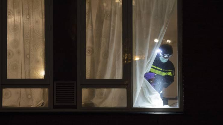Ein Forensiker durchsucht das Haus, in dem der Tatverdächtige verhaftet wurde, nach Hinweisen.