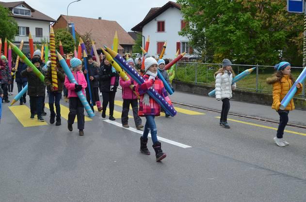 Diese Schüler tragen riesige Farbstifte mit sich herum.