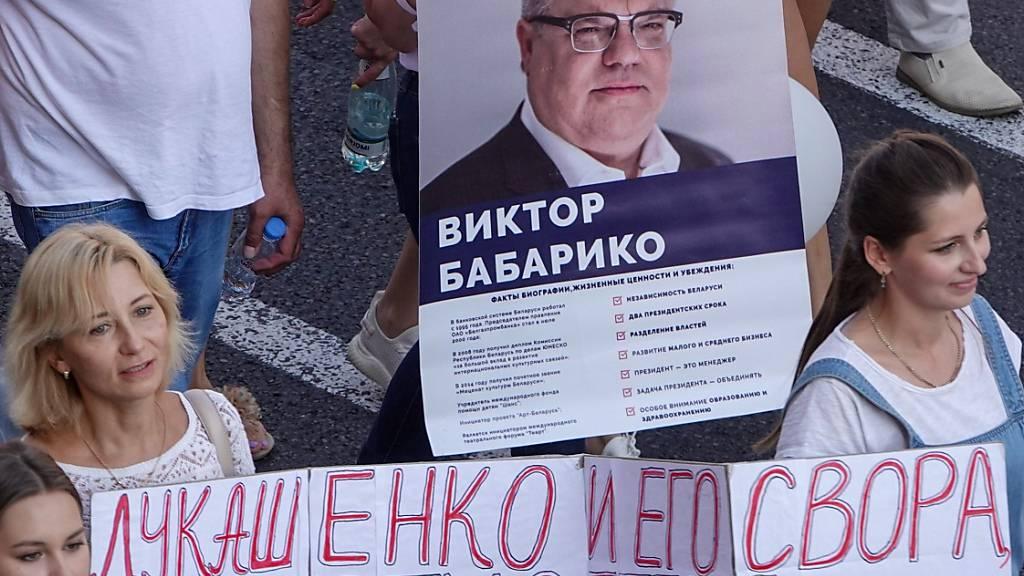 ARCHIV - Menschen protestieren in Minsk gegen den Machthaber Alexander Lukschenko und tragen ein Transparent mit dem Foto von Viktor Babariko, der bei der Präsidentenwahl gegen Lukaschenko antreten wollte. Mehr als ein Jahr nach seiner Festnahme ist der Babariko zu 14 Jahren Straflager verurteilt worden. Foto: Ulf Mauder/dpa