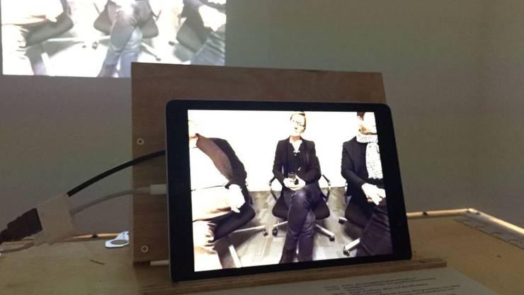 """Die raumgreifende Videoausstellung """"68-88-18"""" dokumentiert die Geschichte der Basler Zwischennutzungen auch mit Hightech: Mit 360-Grad-Technik gefilmte Zeitzeugen-Gesprächsrunden können Besuchende per Tablet so drehen, dass an der Wand ihre Wunschperson zu sehen ist."""