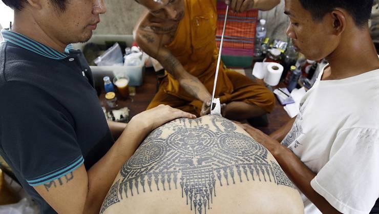 Auf dem traditionellen Tattoo-Fest im Wat-Bang-Phra-Tempel sticht ein buddhistischer Mönch einem Gläubigen mit einem angespitzten Stahlstab ein neues Tattoo.