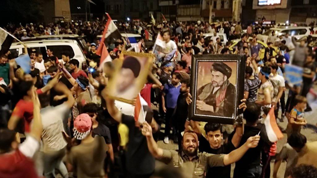 Anhänger schiitischen Predigers Moktada al-Sadr feiern auf den Strassen in Bagdad schon seinen Wahlsieg bei den Parlamentswahlen - obwohl das offizielle Endergebnis noch nicht feststeht.