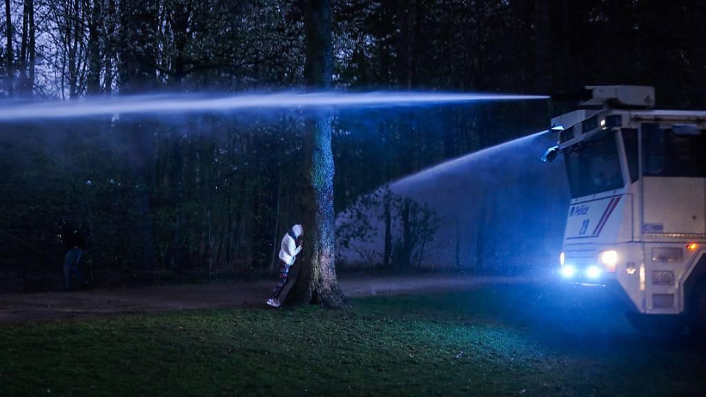 Ein Demonstrant geht hinter einen Baum in Deckung, als die Polizei einen Wasserwerfer einsetzt.