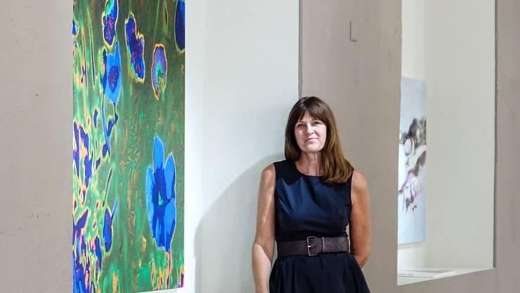 Claudia Mauthe in neben einem Bild von Annelis Štrba in der im Mai eröffneten Popup-Galerie in Locarno.