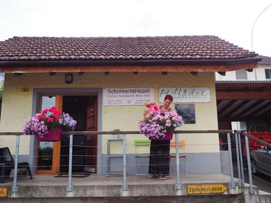 Niole Felber giesst die Blumen vor ihrem Coiffeursalon.