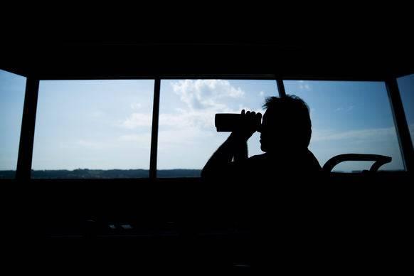 Ein Fluglotse blickt mit einem Fernglas aus dem Tower.