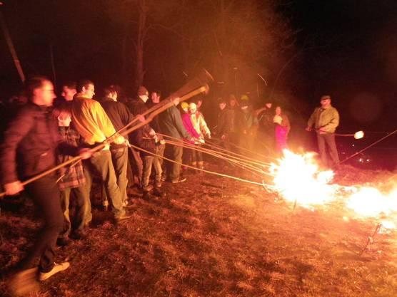 Das Feuer hat sein Werk getan, das Rad ist eingestürzt und die Brandreste werden genutzt zum Anzünden der Scheiben.