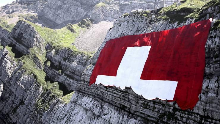 Kletterer rollen die grösste Schweizer Fahne der Welt (80×80 Meter) am Säntis aus. Wie aber gehts mit der Swissness, der Marke Schweiz, weiter? Rauf oder runter?key