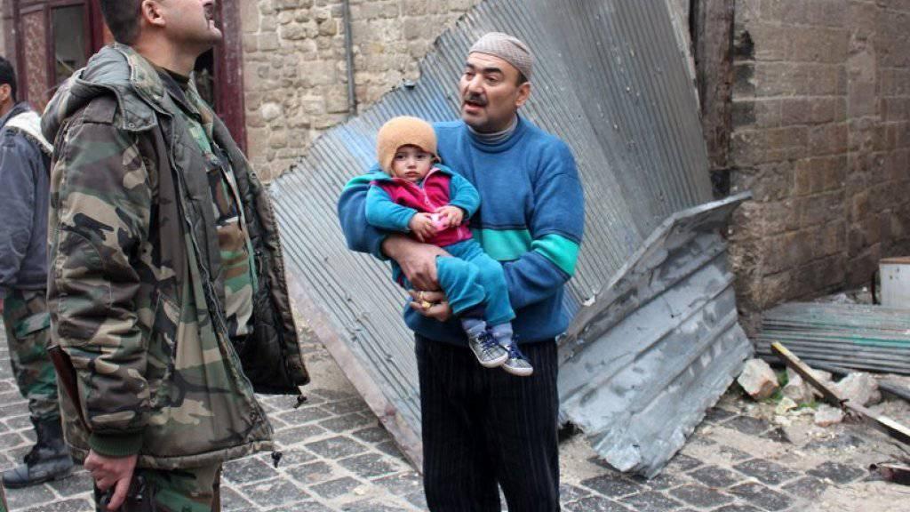 Bewohner von Aleppo im Gespräch mit einem syrischen Soldaten: Die Rebellen haben ihre Waffen gestreckt.