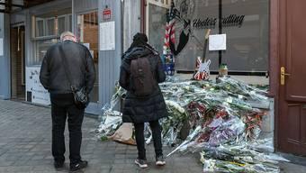 Passanten stehen vor einem Berg von Blumen, die vor einem Friseurladen liegen. Die 24-jährige Besitzerin beging Selbstmord, weil sie ihr neu eröffnetes Geschäft während der zweiten Corona-Welle wieder schließen musste. Foto: Bernard Gillet/BELGA/dpa