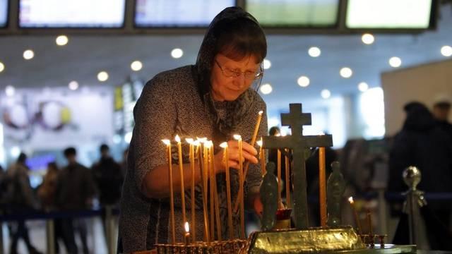 Eine Frau zündet am Flughafen Domodedowo eine Kerze an, um der Opfer des Anschlags zu gedenken