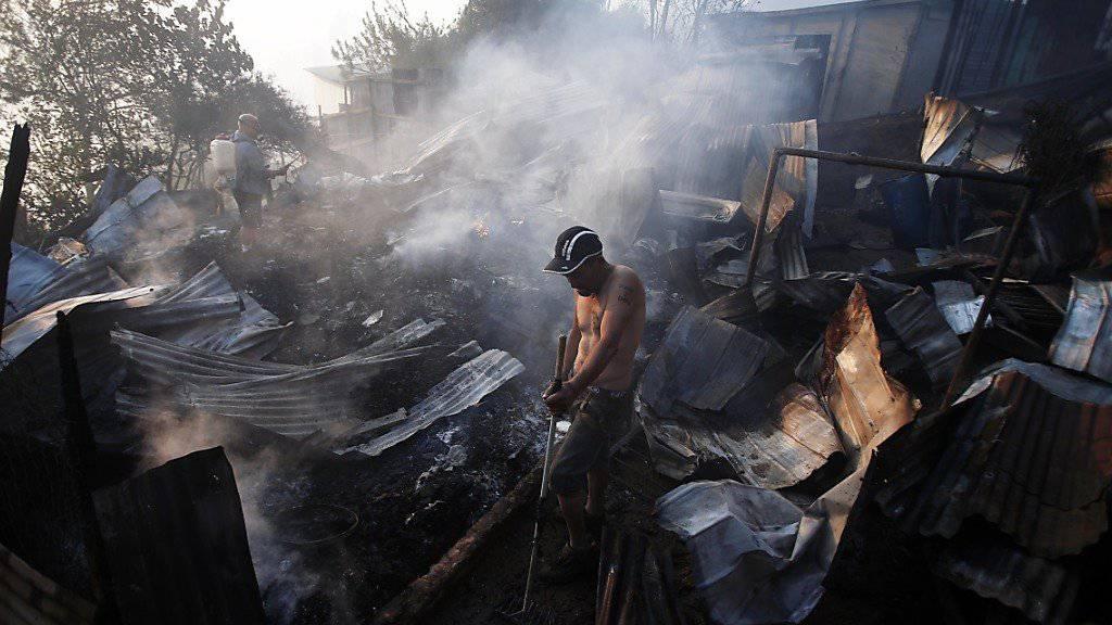 Ein Mann steht zwischen den Ruinen seines abgebrannten Hauses: Der Waldbrand zerstörte 222 Häuser in Valparaíso.