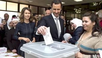 Präsident Assad (M) uns seine Frau (l) legen in Damaskus ihre Wahlzettel in die Urne: Nur in Gebieten Syriens, die unter der Kontrolle der Regierung sind, wurde gewählt.