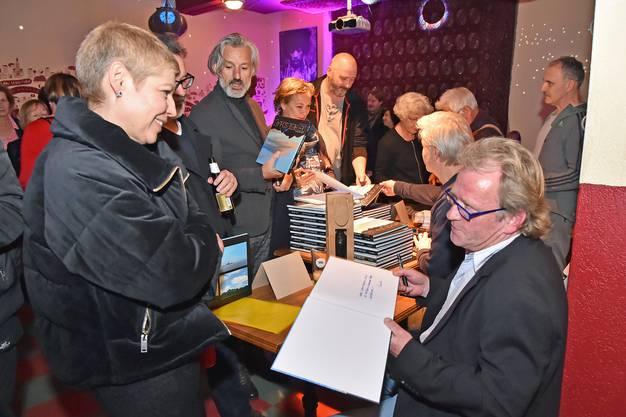 Daniel Portmann signiert an der Vernissage den Bildband «Der Riese schläft».
