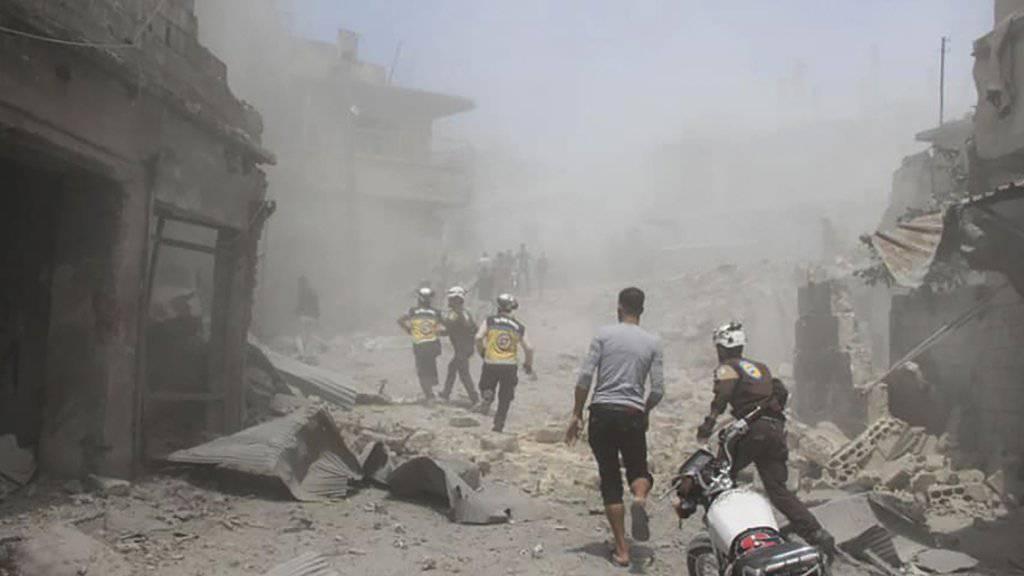 Mitarbeiter der Hilfsorganisation Weisshelme suchen nach einem Luftangriff in der Provinz Idlib nach Überlebenden. (Bild: Hilfsorganisation Weisshelme via AP/Keystone)