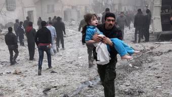 Mann in Aleppo trägt nach einem Bombenanschlag ein Kind aus den Trümmern (Archiv)