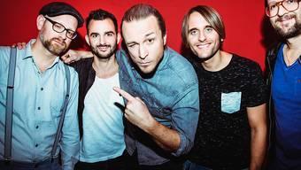 """Die Luzerner Band Dada ante portas ist mit ihrem achten Album unterwegs - Sänger Pirmin """"Pee"""" Wirz (Mitte) ausserdem mit einem rosaroten Schweinchen. (Pressebild)"""