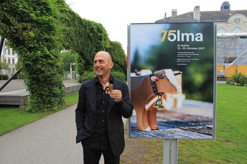 Andreas Tschachtli und die Spielzeug-Kuh seiner Tochter vor dem aktuellen Olma-Plakat. (Bild: zVg)