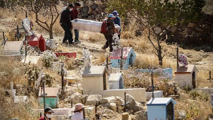 ARCHIV - Menschen mit Mundschutzmasken tragen inmitten der Corona-Pandemie einen Sarg bei einre Beerdigung auf dem Friedhof El Cebollar in Peru. Foto: Denis Mayhua/dpa