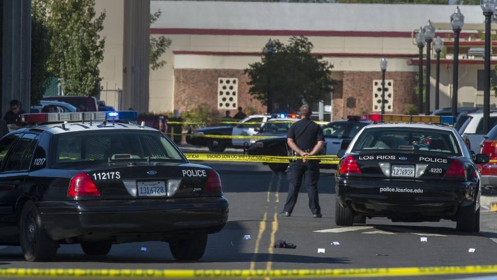 Ein Polizist hält nach einer Schiesserei auf dem Sacramento-College wache.