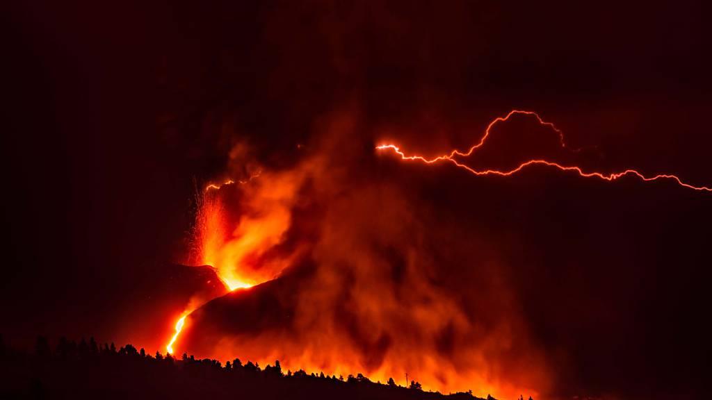 Ein vulkanischer Blitz über dem Vulkan Cumbre Vieja auf La Palma ist trotz des dichten, dunklen Rauchs, der aus dem Krater aufsteigt, von weitem sichtbar. Foto: Europa Press/EUROPA PRESS/dpa