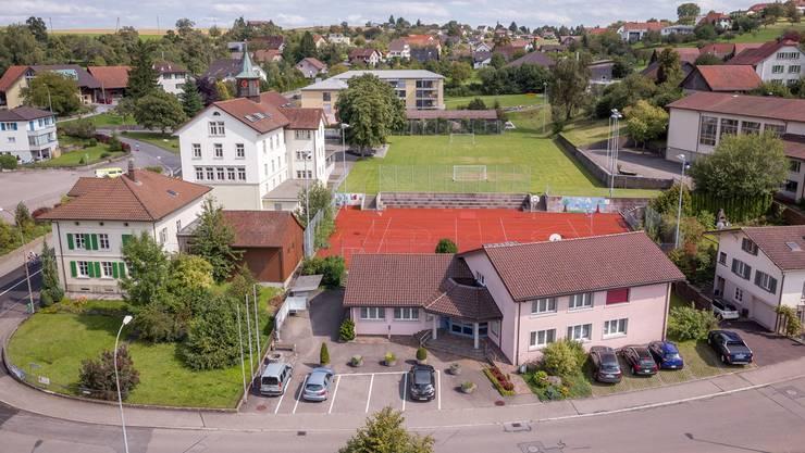 Zwischen das Beck-Bertschi-Haus (vorne links) und das Gemeindehaus käme das neue Schulhaus zu stehen. Das alte Schulhaus (mit Türmchen) soll mittelfristig und die Mehrzweckhalle (Mitte, rechts) rasch saniert werden. (Archiv)
