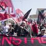 Diese Gewerkschafter protestieren auf der Mittleren Brücke in Basel mit Unia-Fahnen gegen die Unia. Die schwarzen Fahnen und Banner werben für die Protestgewerkschaft Basis 21.