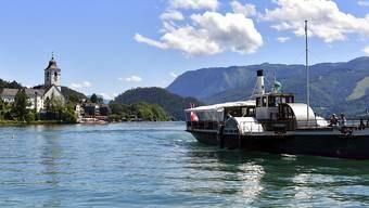 Ein Boot fährt über den Wolfgangsee. Foto: Kerstin Joensson/AP/dpa