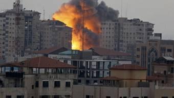 Feuerbrunst über dem zerstörten Hochhaus in Gaza