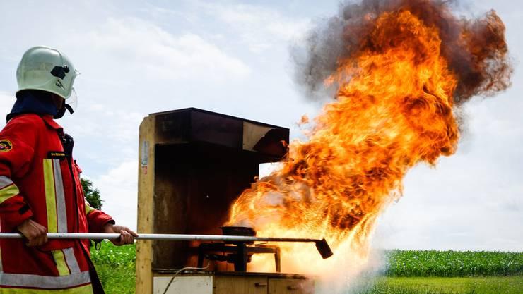 In Lenzburg ist Fritieröl in Brand geraten. Auf dem Foto demonstriert ein Feuerwehrmann, was bei einem Ölbrand passieren kann, wenn man versucht, ihn mit Wasser zu löschen. (Archiv)