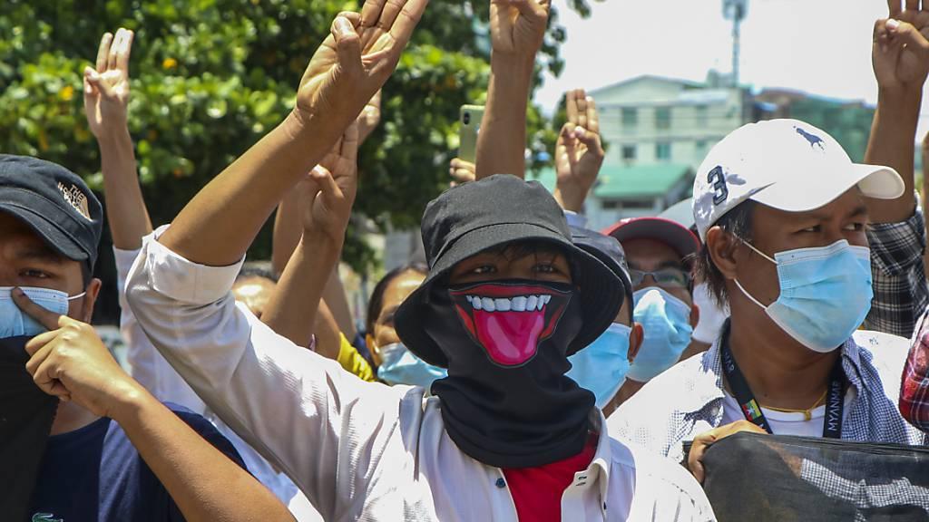 Demonstranten zeigen den Drei-Finger-Gruß, zum Zeichen des Widerstands, bei einer Protestaktion gegen den Militärputsch in Myanmar. Foto: Uncredited/AP/dpa