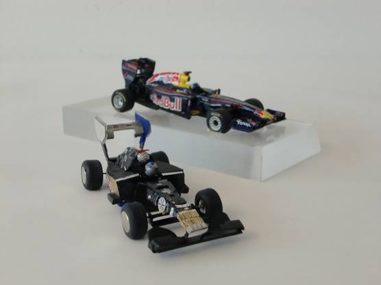 Das Vorbild, hinten, und das Modell des Rennwagens aus vorgegebenen Uhrenbestandteilen