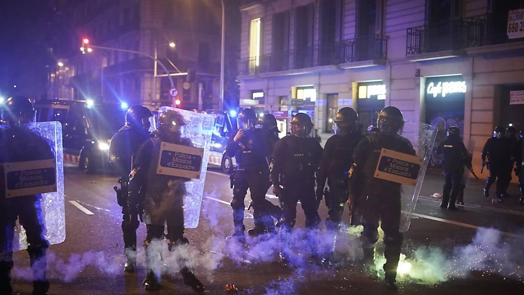 Feuerwerkskörper explodieren neben Polizisten während eines Protests gegen die Verhaftung des Rappers Pablo Hasel. Foto: Joan Mateu/AP/dpa