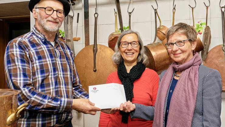 Annarös Vonlanthen (Mitte) und Evi Hostettler (rechts) erhalten von Urs Bucher die Suppentag-Kollekte überreicht (Bild: Alwin Gasser)