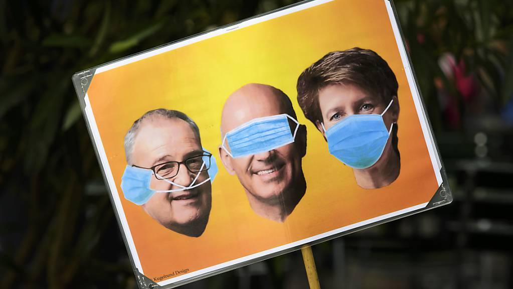 Drei Affen im Bundesrat? - Ein Schild, das Kritiker der Covid-19-Verordnung der Landesregierung am Samstag an der Demonstration in Bern mit sich führten. Vor dem Bundeshaus schienen die Polizisten zeitweise in der Überzahl.