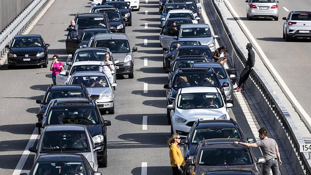 Warten auf die Ferien: Autofahrerinnen und Autofahrer im Stau vor dem Gotthard-Nordportal. (Archivbild)