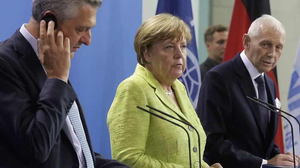 Bundeskanzlerin Angela Merkel vor den Medien mit UNO-Flüchtlingshochkommissar Filippo Grandi (l) und IOM-Generadirektor William Lacy Swing (r)