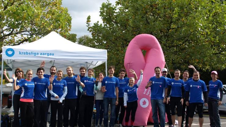 Die laufsportbegeisterten des Krebsliga-Teams vor der rosa Brustkrebs-Solidaritätsschleife.