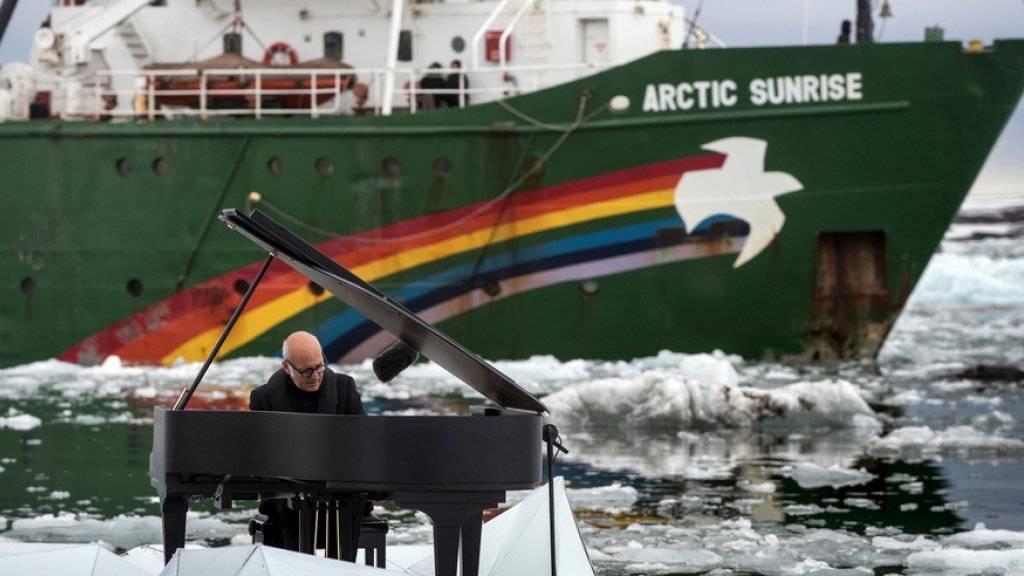 Eis und Wasser können seinem Engagement für die Arktis nichts anhaben: Der italienische Pianist Ludovico Einaudi spielt auf einer künstlichen Eisscholle in Norwegen. Im Hintergrund ankert das Greenpeace-Schiff «Arctic Sunrise».