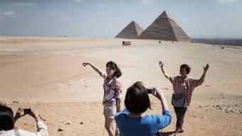 Touristen posieren vor den Pyramiden von Gizeh in der Nähe von Kairo.