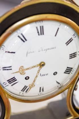 Die aus schwarz gefasstem Fichtenholz und mit Blattgoldstäben verzierte Pendule stammt aus dem Jahre 1820. Gebaut wurde sie von den Gebrüdern Hagnauer in Aarau. Hinter dem aufklappbaren Glastürchen befindet sich das Zifferblatt aus Email, auf welchem «frères Hagnauer ARRAU» steht. Individuelle Schreibweisen von Ortsnamen waren damals nicht unüblich. Im 18. und 19. Jahrhundert waren in Aarau insgesamt 35 Personen in der Uhrenherstellung tätig.