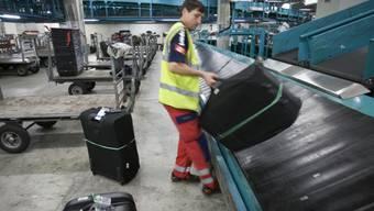 Ein Mitarbeiter von Swissport lädt Gepäck auf ein Band (Archiv)