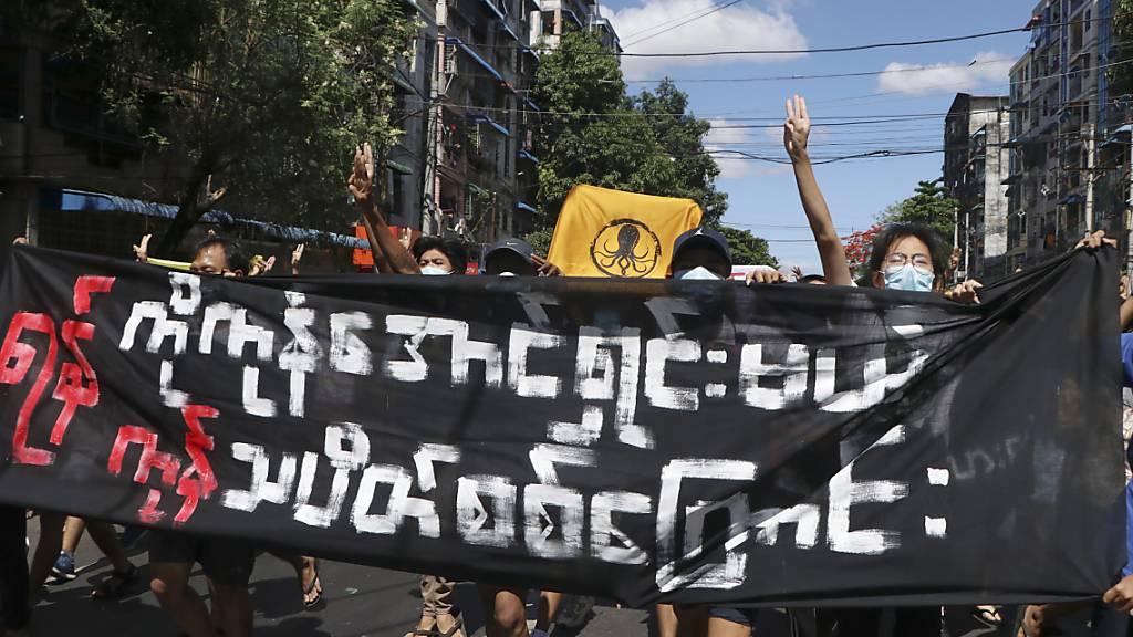 Protestteilnehmer halten während einer Demonstration ein Transparent hoch und zeigen das Drei-Finger-Zeichen des Widerstandes. Vier Monate nach dem Militärputsch in Myanmar kommt das Land weiter nicht zur Ruhe. Foto: Uncredited/AP/dpa