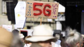 Personen protestieren mit Plakaten während eine Demonstration gegen die Einführung von 5G auf dem Bundesplatz in Bern.