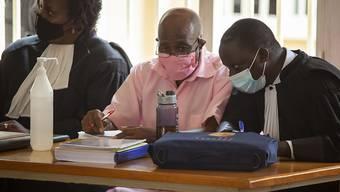 Paul Rusesabagina sitzt zwischen seinen Anwälten bei einer Anhörung in Kigali. Foto: Muhizi Olivier/AP/dpa