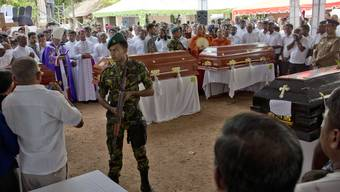 A soldier stands guard during a funeral service attended by Cardinal Malcolm Ranjith for Easter Sunday bomb blast victims at St. Sebastian Church in Negombo, Sri Lanka, Tuesday, April 23, 2019. (AP Photo/Gemunu Amarasinghe)