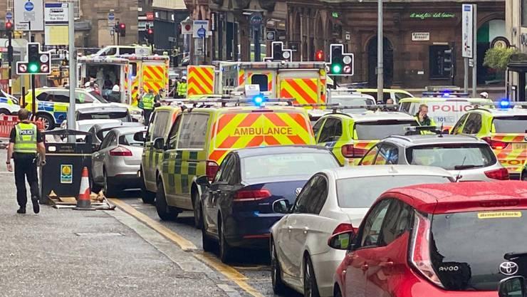 SCREENSHOT - Rettungs- und Polizeifahrzeuge an dem abgesperrten Tatort in der West George Street in Glasgow. Foto: @jatv_Scotland/Twitter/PA Media/dpa - ACHTUNG: Nur zur redaktionellen Verwendung und nur mit vollständiger Nennung des vorstehenden Credits