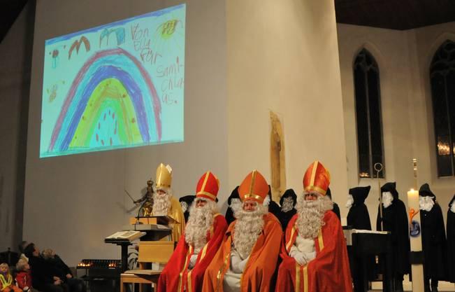 Der Samichlaus zeigt kleine Kunstwerke von Kindern, vorne seine drei Helfer-Chläuse in roten Gewändern
