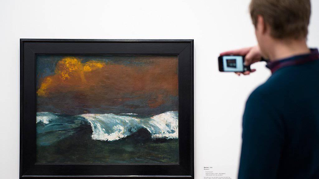 Ein Ausstellungsbesucher macht ein Foto von Emil Noldes Gemälde «Brecher» von 1936. Emil Nolde (1867-1956) ist eine Ikone des Expressionismus. Er war aber auch Unterstützer des Nationalsozialismus. eine Ausstellung  in Berlin setzt sich kritisch mit seinem Werk auseinander. (Archiv)