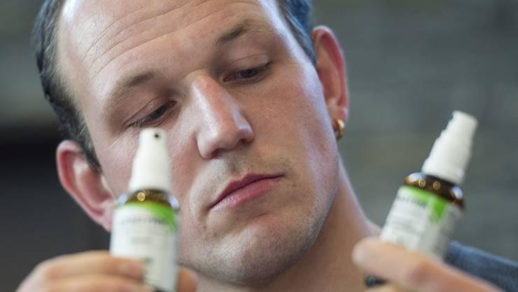 Bruno Gisler hält die beiden verschiedenen Sprays in der Hand.